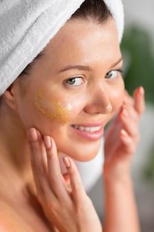 Smiley femme avec une serviette sur la tête appliquant des soins de la peau