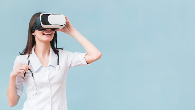Smiley femme avec stéthoscope à l'aide d'un casque de réalité virtuelle