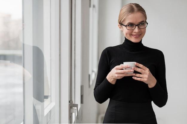 Smiley femme avec une tasse de café