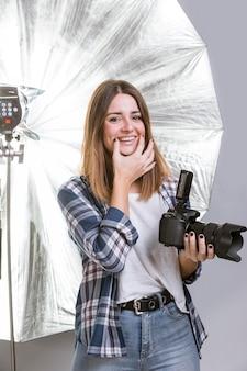 Smiley femme tenant un appareil photo professionnel