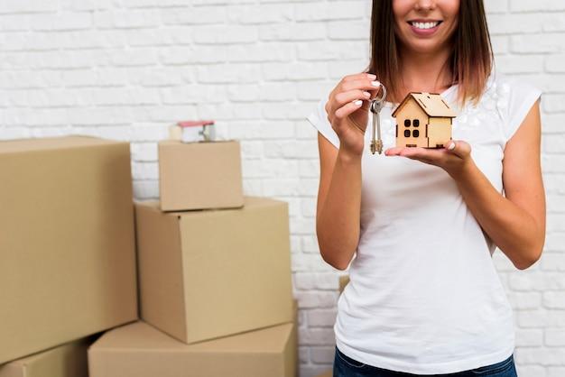 Smiley femme tenant un chalet en bois et des clés