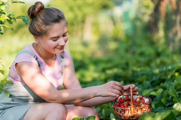 Smiley femme tenant une corbeille de fruits