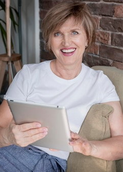Smiley femme tenant un coup moyen de tablette