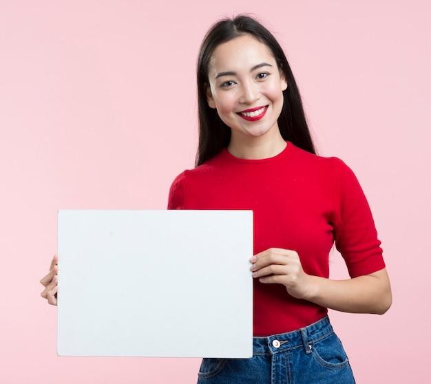 Smiley femme tenant une feuille de papier vierge