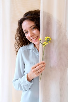 Smiley femme tenant des fleurs coup moyen