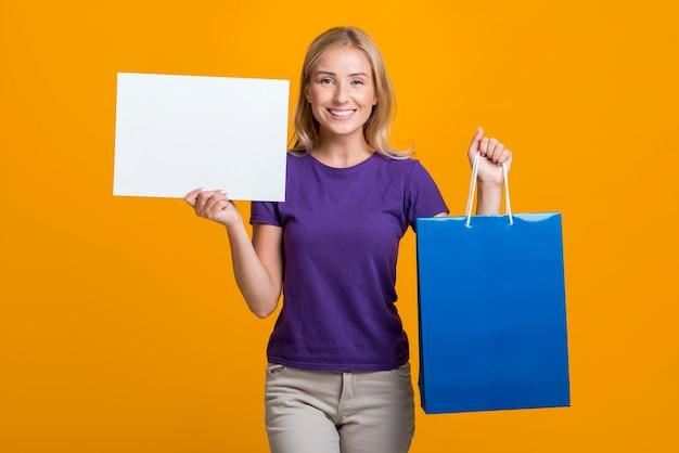 Smiley femme tenant une pancarte blanche et un sac à provisions