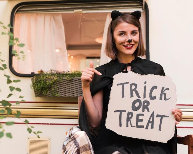 Smiley femme tenant une pancarte d'halloween