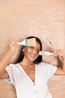 Smiley femme tenant des pinceaux