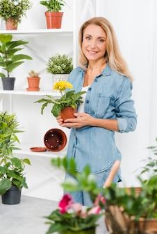 Smiley femme tenant un pot de fleur