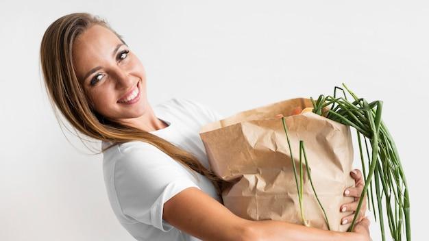 Smiley femme tenant un sac en papier avec des goodies sains