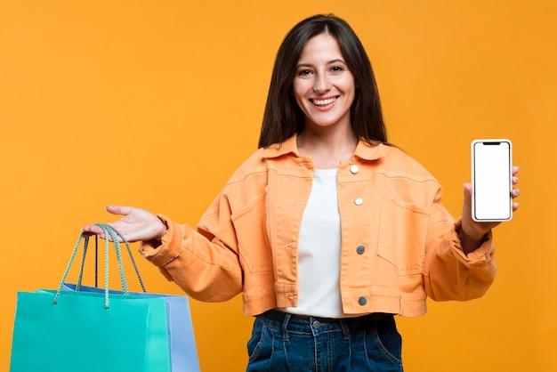 Smiley femme tenant des sacs à provisions et smartphone