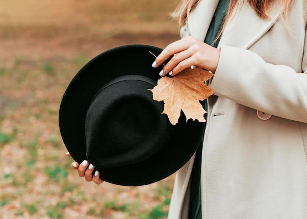 Smiley femme tenant son chapeau noir et un gros plan de feuille