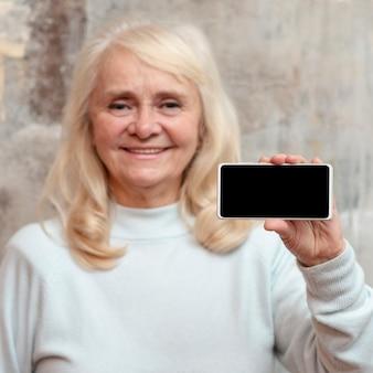 Smiley femme tenant le téléphone