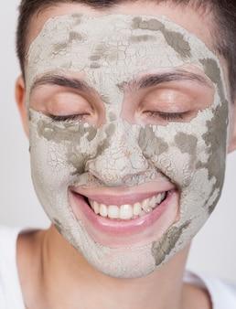 Smiley femme avec un traitement de boue sur le visage
