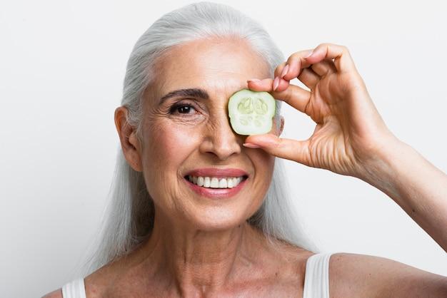 Smiley femme avec une tranche de concombre