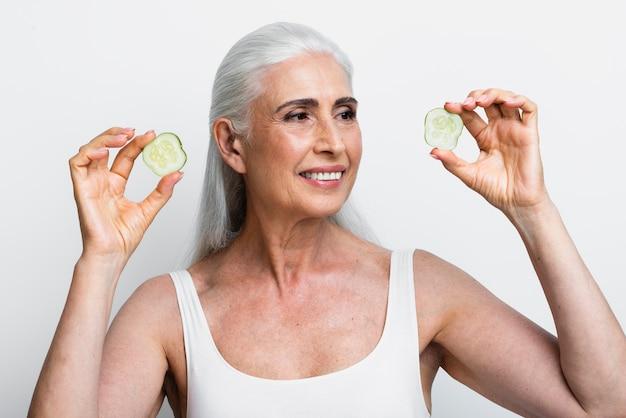 Smiley femme avec des tranches de concombre