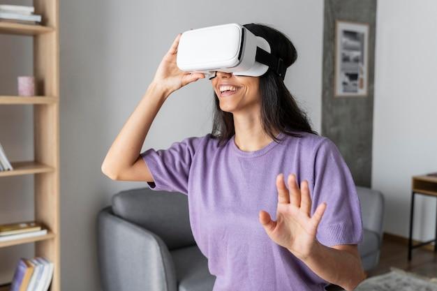 Smiley femme utilisant un casque de réalité virtuelle à la maison