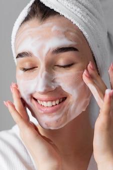 Smiley femme utilisant un produit pour le visage