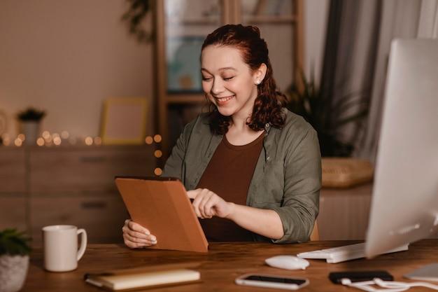 Smiley femme utilisant sa tablette à la maison
