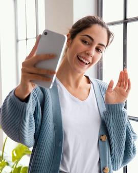 Smiley femme vidéo appelant quelqu'un à l'aide de smartphone à la maison