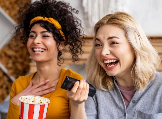 Smiley femmes riant en regardant un film