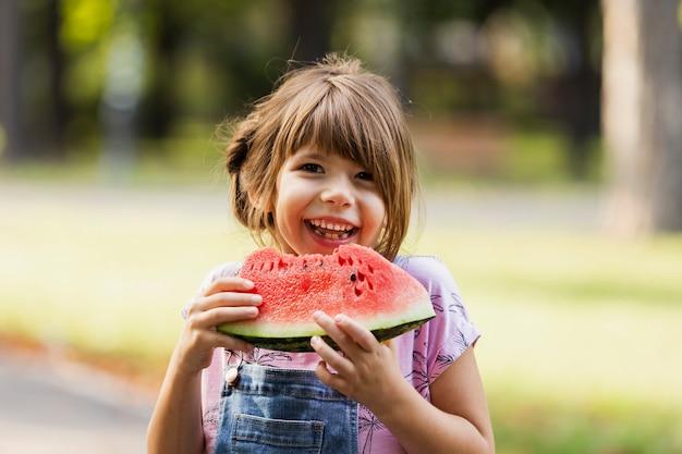 Smiley fille appréciant la pastèque