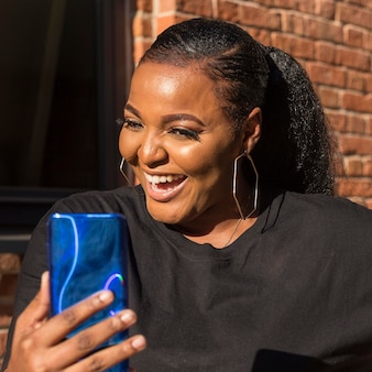 Smiley fille regardant son téléphone gros plan