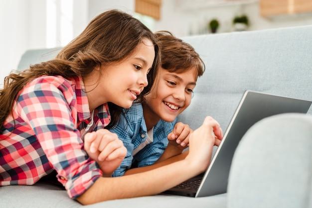 Smiley frères et sœurs sur le canapé à l'aide d'un ordinateur portable