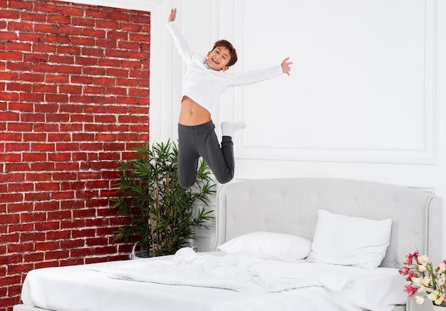 Smiley garçon vue de face, sauter sur le lit