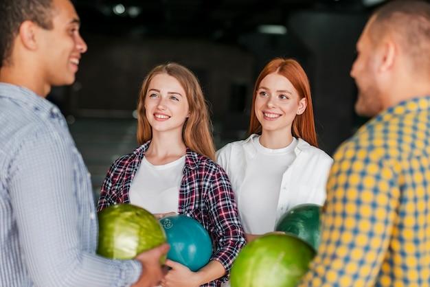 Smiley gens debout dans un club de bowling