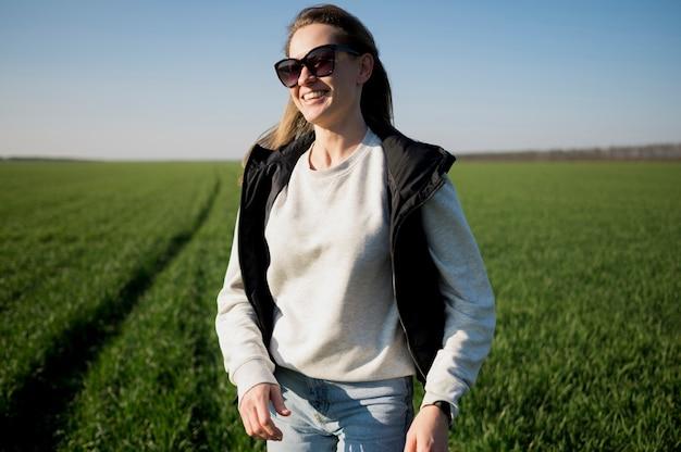 Smiley girl in the field portant des lunettes de soleil