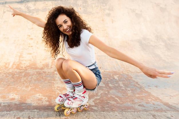 Smiley girl posant dans ses rollers à l'extérieur
