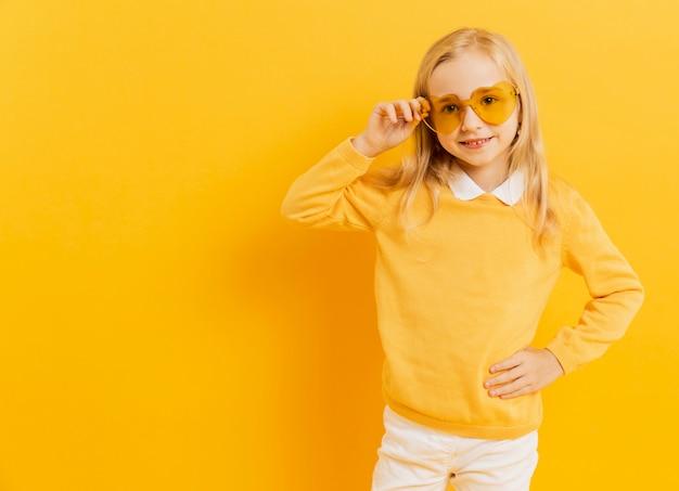 Smiley girl posant tout en portant des lunettes de soleil