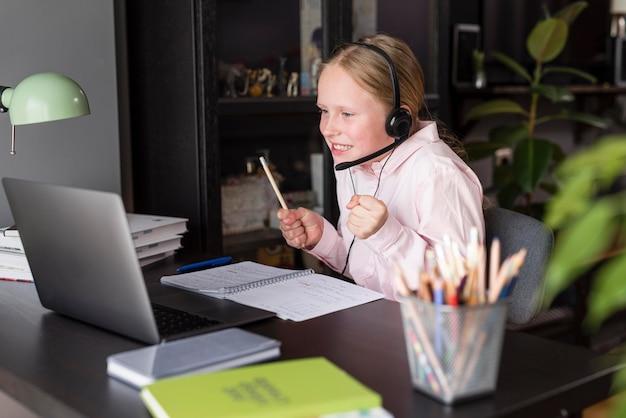 Smiley girl prête attention aux cours en ligne
