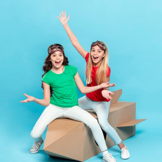 Smiley girls sitting on cartoon flying ship
