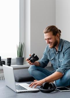 Smiley homme avec appareil photo et ordinateur portable