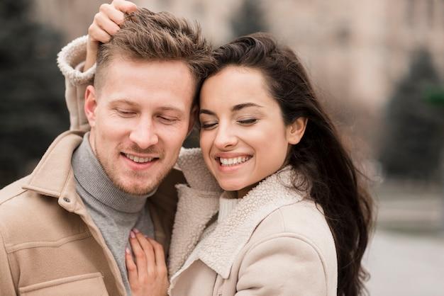 Smiley homme et femme posant à l'extérieur
