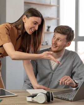 Smiley homme et femme travaillant avec un ordinateur portable et des écouteurs