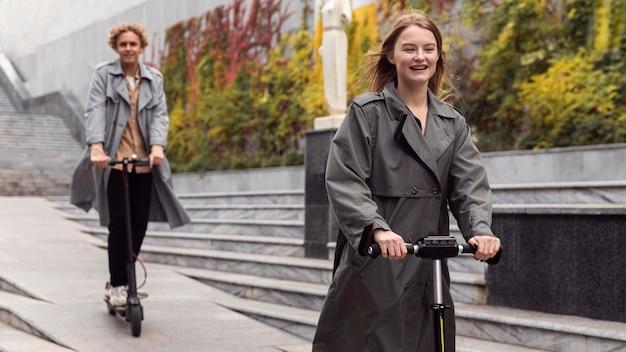 Smiley homme et femme utilisant un scooter électrique à l'extérieur