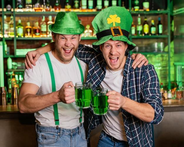 Smiley hommes célébrant st. la journée de patrick au bar
