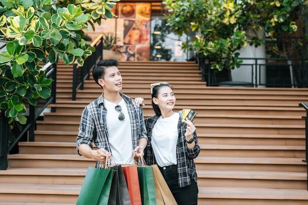 Smiley jeune couple tenant plusieurs sacs à provisions en papier