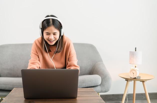 Smiley jeune femme asiatique à l'aide d'un ordinateur portable à la table