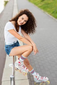 Smiley jeune femme posant avec des rollers