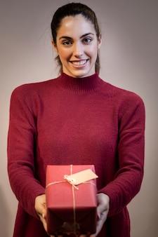Smiley jeune femme tenant un cadeau de noël
