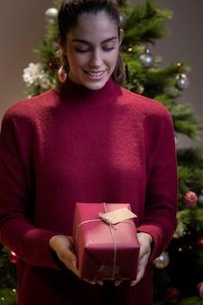 Smiley jeune femme tenant un cadeau