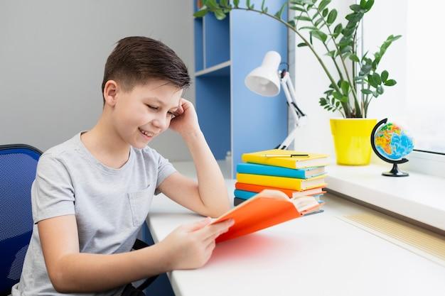 Smiley jeune garçon lisant