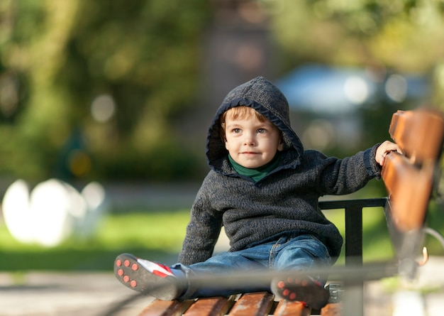 Smiley jeune garçon tenant la main sur un banc