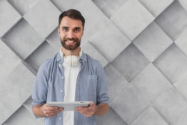 Smiley jeune homme tenant une maquette de tablette