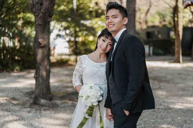 Smiley jeunes mariés posant ensemble à l'extérieur