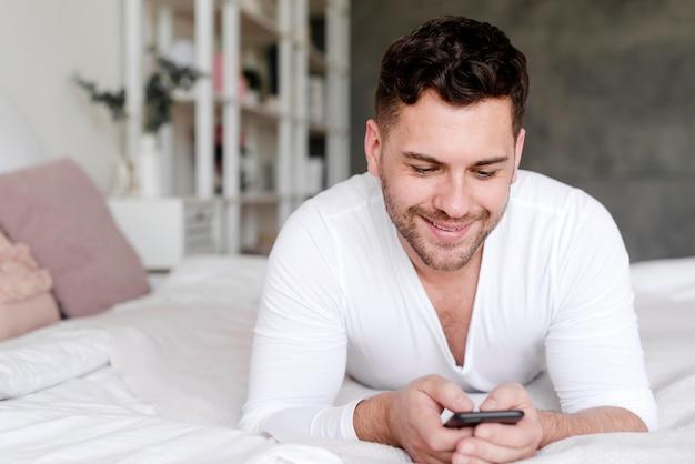 Smiley man holding smartphone